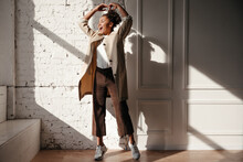 Full Length View Of Black Lady In Trench Coat Posing With Hands Up. Indoor Shot Of Winsome African American Girl Enjoying Sunlight.