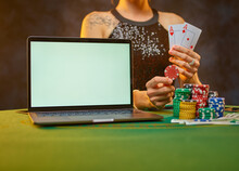 Online Sports Betting. A Young Gambling Woman Bets On The Victory Of Her Favorite Team. Green Background. The Laptop Is On The Table, Chips Are Nearby. A Woman Holds Playing Cards In Her Hands.