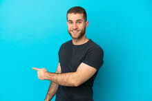 Young Handsome Caucasian Man Isolated On Blue Background Pointing Back