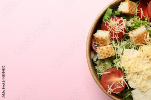 Fototapeta Paper bowl with Caesar salad on pink background