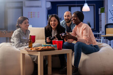 Multi Ethnic Diverse Group Of Friends Playing Fun Game On Tv Console After Work At Office. Cheerful Colleagues Holding Joystick Controller For Gaming Indoors On Sofa. Happy Team Celebrating