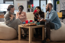 Diverse Group Of Colleagues Enjoy After Work Celebration Drinks At Office. Multi Ethnic Cheerful Friends Sitting On Couch With Snacks Pizza Chips And Cups Bottles Of Beer Alcohol On Table.