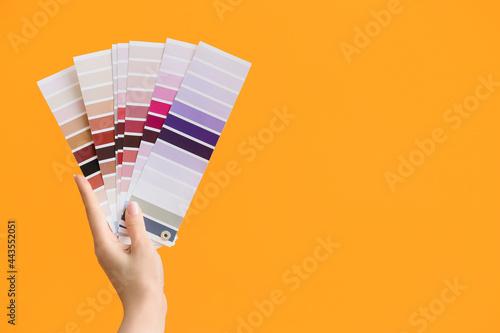 Obraz na plátně Female hand and paint color palettes on color background