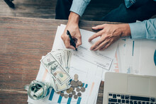 Business Man Hand Writing And Signing White Blank Bank Check Book And Dollar Bill, Coin, Laptop And Graph Chart On The Desk At Office. Payment By Check, Paycheck, Payroll Concept.