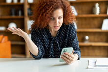Shocked Red-haired Curly Woman Holding A Smartphone, Feel Astonishment With A Bad News, Fired From Work, Irritated Female Eoffice Employee Looks At Phone Screen And Does Not Understand What Happened