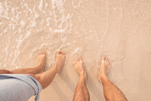 Legs And Feet Of A Man And A Woman Of A Couple In Love On A Sandy Beach By The Sea