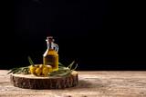 Fototapeta Kawa jest smaczna - Virgin olive oil bottle and green olives on wooden table. Copy space