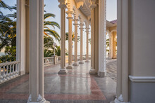 Columns And Marble Floor Of The Ghagra Colonnade At Sunset. The Historical Architectural Structure Opens The Scenic View Of The Black Sea And Its Coast With Palms. Landscapes, Travel, Tourism.