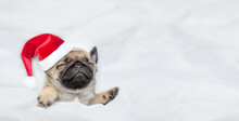 Funny Pug Puppy Wearing Red Santa Hat Sleeps Under White Blanket At Home. Top Down View. Empty Space For Text
