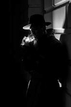 Dark Dramatic Silhouette Of A Man In A Hat Smoking A Cigarette On The Street At Night