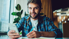 Portrait Of Handsome Caucasian Student With Education Copybook And Modern Mobile Device Posing At University Desktop, Young Hipster Guy With Smartphone Gadget Studying In College Classmate