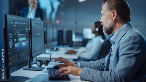 Fotografiet Portrait of Serious Professional Technical Controller Sitting at His Desk with Multiple Computer Displays Before Him