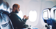 Male Sitting On Airplane While Using Cellphone