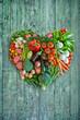 Herz aus Gemüse. Veganer Essen auf retro vintage Holz Hintergrund