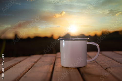 Fotografie, Obraz coffee cup on the wooden table with the sunrise background