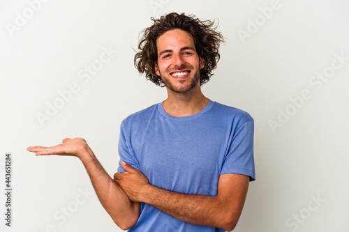 Leinwand Poster Young caucasian man isolated on white background showing a copy space on a palm and holding another hand on waist