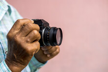 Both Hands Of An Elderly Thai Man Holding An Old Film Camera.