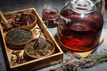 Dry Tea Leaves, Raspberries And Tea In A Glass Teapot