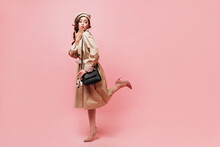 Full-length Shot Of Lady In Midi Trench Coat Coquettishly Lifting Leg And Blowing Kiss On Pink Background