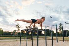 Female Athlete Training On Parallel Bars In A Calisthenic Park