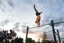 Male Athlete Doing Handstand On A Bar In A Calisthenic Park