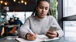 Leinwandbild Motiv African American female student with education textbook using cellphone application for informative research during course work learning in coffee shop, intelligent millennial with smartphone