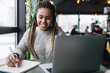 Leinwandbild Motiv African American female freelancer spending time for working remotely with startup project checking noted information in education textbook, cheerful student smiling while e learning via laptop