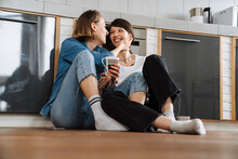 A Smiling Lesbian Couple Looking To Each Other While Sitting On The Floor With A Cup