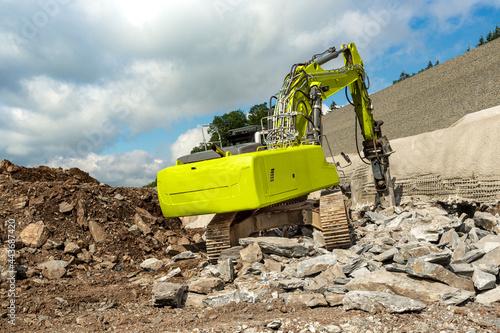 Fotografija A yellow excavator with hydraulic hammer chisels rocks