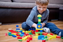 A Young Builder. Kid Building City From Wooden Blocks. Kids Play Room. Development And Construction Concept. Toy To Learn Stimulates Imagination, Creativity, Hand-eye Coordination.