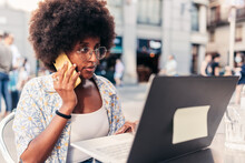 Afro Young Woman Calling From A Bar Terrace. She Is Using A Yellow Telephone And Looks To A Modern Laptop
