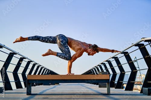 Fototapeta Fit man doing a hand stand while practicing yoga alone near the ocean against sk