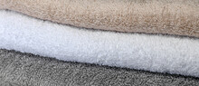 The Background Is A Set Of Terry Cotton Towels Gray Beige White.