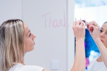 Blonde Woman Drawing On Mirror With Lipstick. Message For A Loved One.