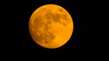 An Orange Moon Surrounded By The Darkness Of The Night