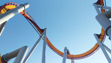 Empty Twisting Roller Coaster Tracks Against Blue Sky