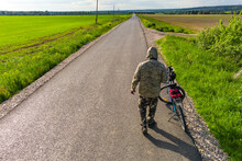 A Cyclist In Camouflage From The Back Next To A Bicycle On The Background Of An Asphalt Road Going Into The Distance