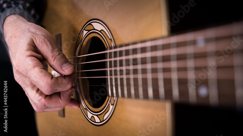 Fotografia, Obraz Person playing the acoustic guitar close up of guitar strings and hand