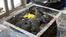 A Glowing Piles Of Charcoal Briquettes Using Fire Starter Inside Of Black Portable Mini Picnic Barbeque Grill Box. BBQ Preparation.