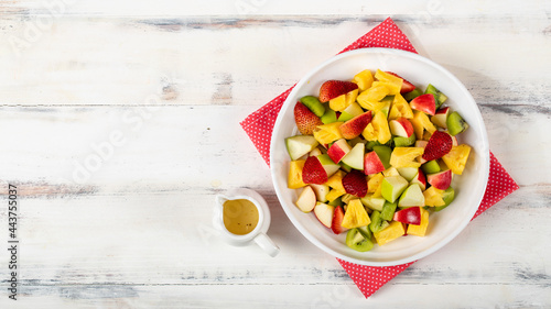 Fotografie, Obraz Mixed fruits salad including strawberry, kiwi, apple, and pineapple in white dish place on sackcloth on wooded table