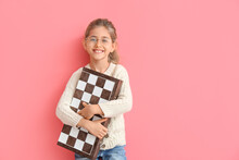 Cute Little Girl With Chessboard On Color Background