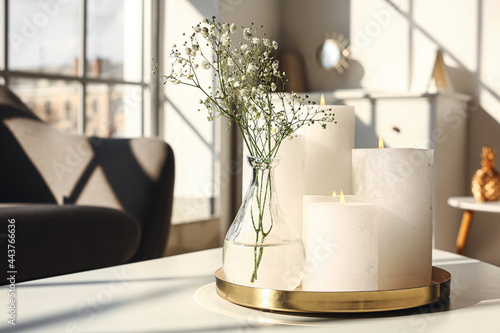Fotografie, Obraz Tray with candles and flowers on table in living room