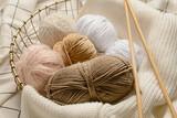 Fototapeta Kawa jest smaczna - Basket with knitting yarn and needles on fabric background, closeup