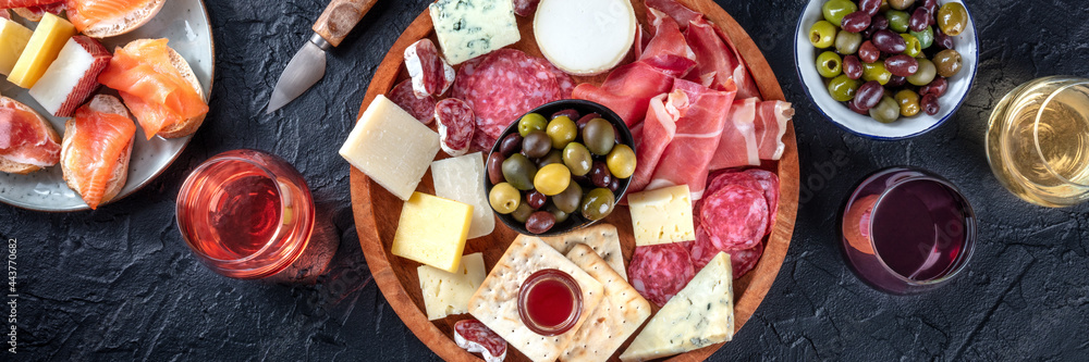 Obraz Italian antipasti or Spanish tapas panorama. Gourmet cold meat and cheese platter on a table, shot from the top with wine on a black background. A variety of appetizers fototapeta, plakat