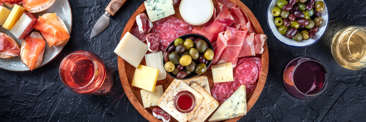 Italian antipasti or Spanish tapas panorama. Gourmet cold meat and cheese platter on a table, shot from the top with wine on a black background. A variety of appetizers