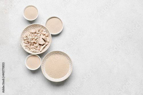 Fototapeta Bowls with fresh and dry yeast on light background
