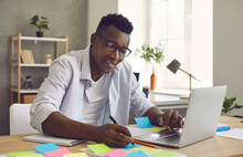 Focused African American Man Writes Notes On Colorful Stickers While Developing A Business Project In The Office. Concept Of Brainstorming, Creative Thinking And Drawing Up A Startup Plan.