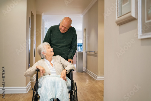 Fototapeta Senior man visit disabled woman on wheelchair at nursing home
