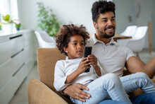 Family, Fatherhood Love People Concept. Happy Father And Daughter Watching Tv At Home