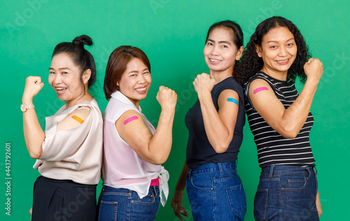 Canvastavla Four middle aged Asian women showing their arms with bandage patch showing they got vaccinated for Covid 19 virus on green background